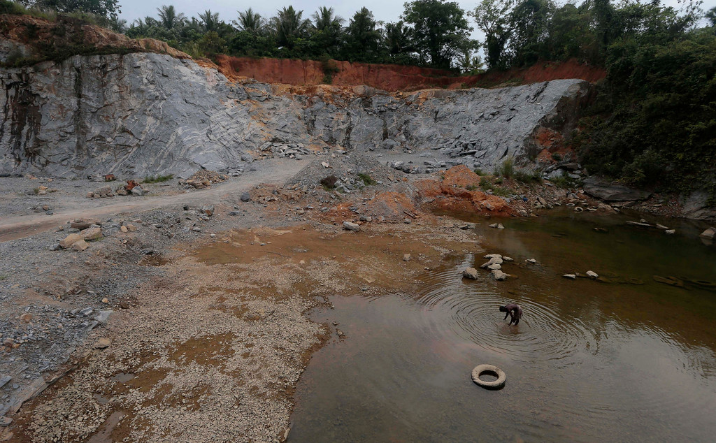 . A Sri Lankan quarry worker takes a wash in a pool of stagnant rainwater at a stone quarry on Earth Day in Athurugiriya, on the outskirts of Colombo, Sri Lanka, Tuesday, April 22, 2014. (AP Photo/Eranga Jayawardena)
