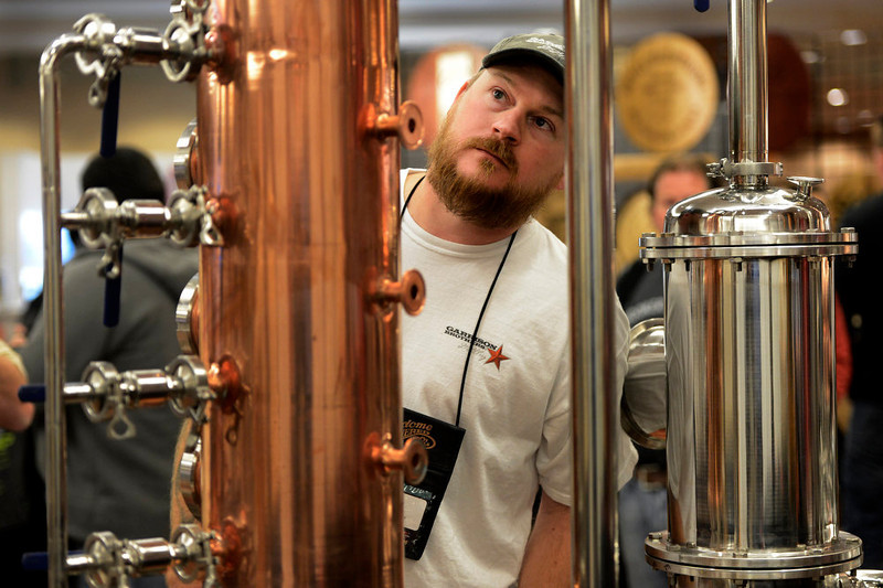 . Master Distiller, Donnis Todd, of Hye, TX, examines a still displayed by Artisan Still Design during the American Distilling Institute\'s 10th Annual Craft Spirits Conference & Vendors Expo at the downtown Sheraton in Denver, CO April 02, 2013. DSTILL  expects more than 900 visitors during the weeklong celebration, making it the country�s largest rally of independent distillers.   (Photo By Craig F. Walker/The Denver Post)