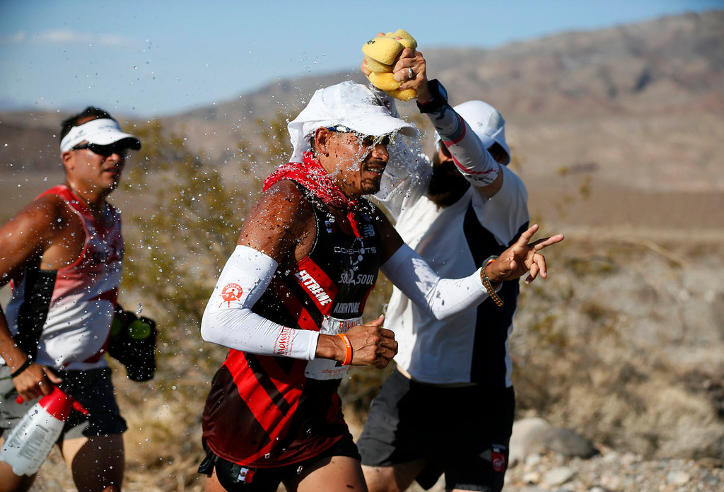 . Oswaldo Lopez of Mexico, 41, (C) is doused with water during the Badwater Ultramarathon in Death Valley National Park, California July 15, 2013. The 135-mile (217 km) race, which bills itself as the world\'s toughest foot race, goes from Death Valley to Mt. Whitney, California in temperatures which can reach 130 degrees Fahrenheit (55 Celsius).  REUTERS/Lucy Nicholson