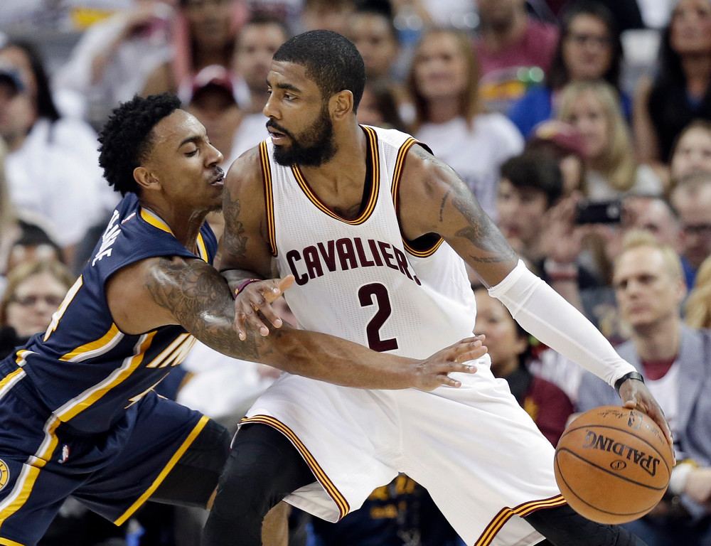 . Indiana Pacers\' Jeff Teague, left, reaches in as Cleveland Cavaliers\' Kyrie Irving drives to the basket in the second half in Game 1 of a first-round NBA basketball playoff series, Saturday, April 15, 2017, in Cleveland. (AP Photo/Tony Dejak)