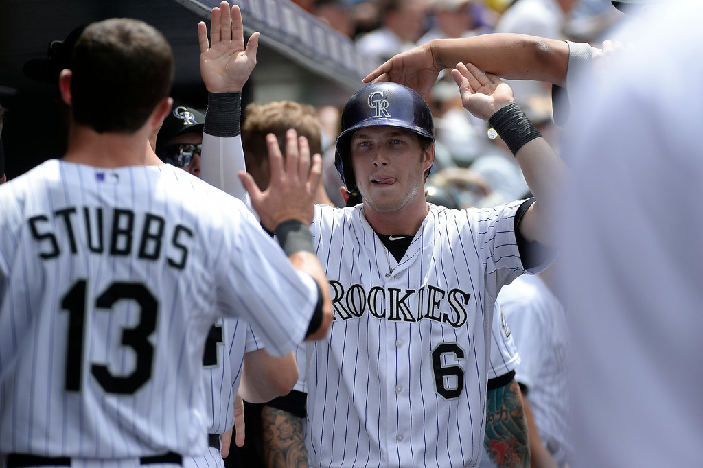 . Colorado Rockies left fielder Corey Dickerson (6) high fives in the dugout after scoring on a Colorado Rockies second baseman DJ LeMahieu (9) single in the fourth inning against the St. Louis Cardinals June 25, 2014 at Coors Field. (Photo by John Leyba/The Denver Post)