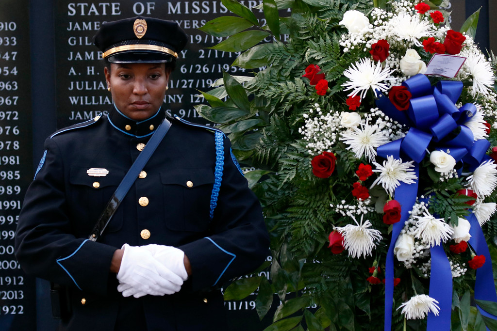 . Jackson Police Officer Stephanie Horn stands vigil along side the wreath placed at the Statewide Fallen Officers Memorial during the Mississippi Law Enforcement Memorial Candlelight Vigil in Jackson, Miss., Tuesday, May 15, 2018. (AP Photo/Rogelio V. Solis)