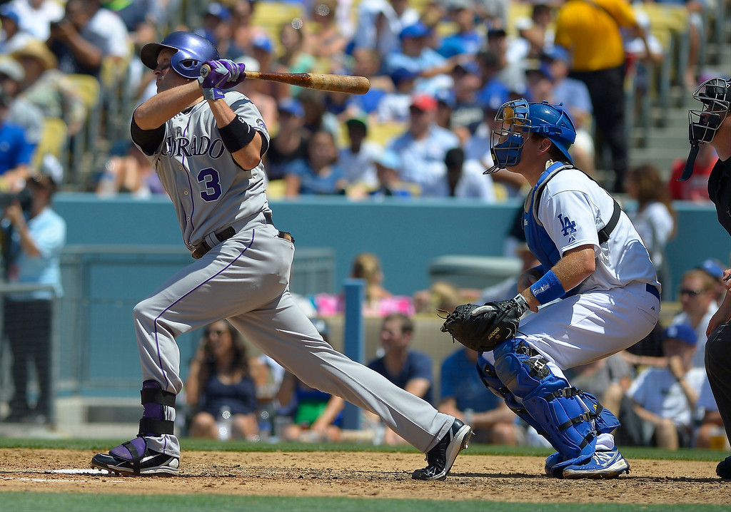 . Colorado Rockies\' Michael Cuddyer, left, hits a two-run home run as Los Angeles Dodgers catcher A.J. Ellis looks on during the fifth inning of a baseball game on Sunday, July 14, 2013, in Los Angeles. (AP Photo/Mark J. Terrill)