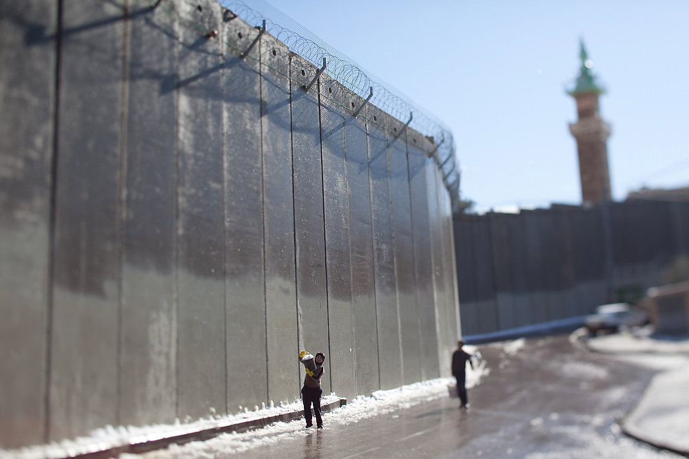 Description of . Palestinian children play with snow in front of the controversial Israeli separation barrier on January 10, 2013 in the West Bank village of Abu Dis, at the outskirts of Jerusalem. (Photo by Uriel Sinai/Getty Images)