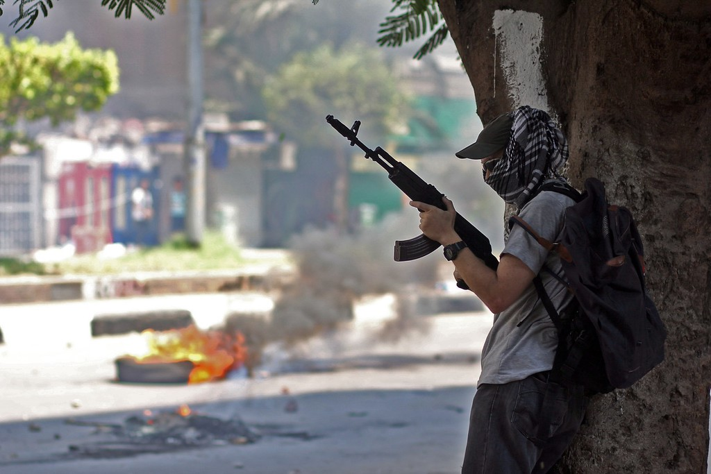 . An armed middle-aged supporter of ousted President Mohammed Morsi takes cover behind a tree in the Mohandeseen district of  Cairo, Egypt, Wednesday, Aug. 14, 2013.  (AP Photo/Roger Anis, El Shorouk Newspaper)