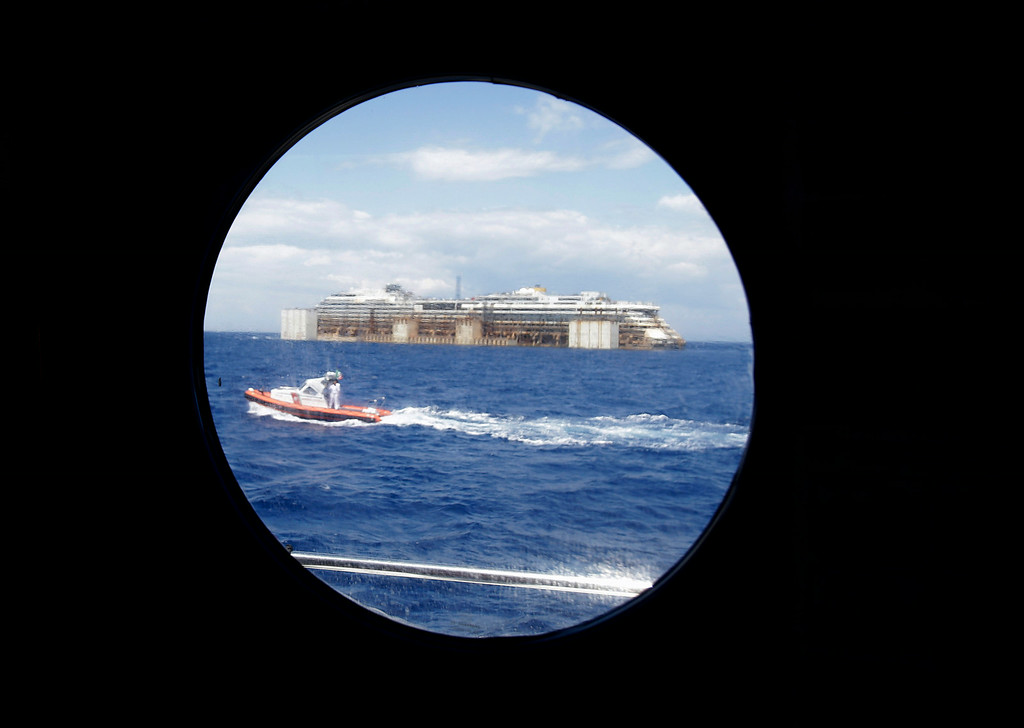 . The wreck of the Costa Concordia cruise ship is seen through a porthole as it is towed by two tugboats away from the Tuscan island of Isola del Giglio,  Italy, Wednesday, July 23, 2014. The Costa Concordia cruise liner has begun its final voyage away from the tiny Italian island where it capsized on Jan. 13, 2012, killing 32 people. (AP Photo/Gregorio Borgia)