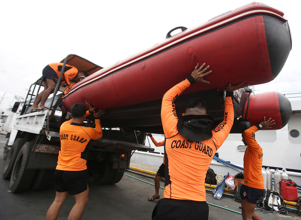 . Philippine Coast Guard divers bring down a rubber boat as they prepare to be deployed to augment rescue operations in Cebu from their headquarters in Manila, Philippines on Saturday, Aug. 17, 2013. A ferry with more than 800 people aboard sank near the central Philippine port of Cebu after colliding with a cargo vessel, killing at least 28 people. Hundreds have been rescued but more than 200 are still missing, the coast guard said Saturday. (AP Photo/Aaron Favila)
