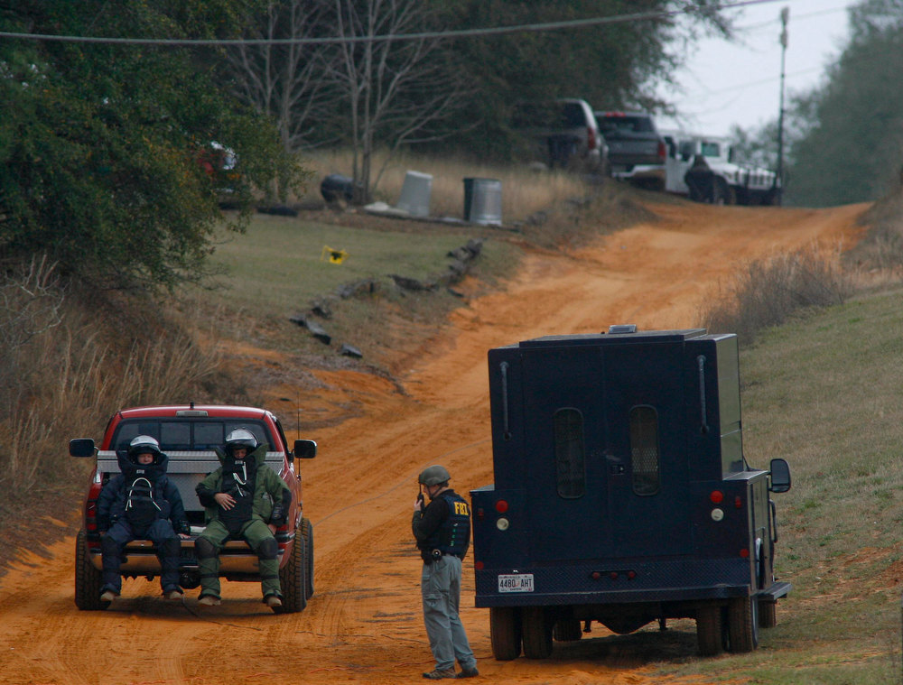 Description of . Law enforcement officials in bomb squad protective gear are driven to the scene of a shooting and the bunker as the standoff with the shooter continues in Midland City, Alabama January 30, 2013. A standoff continued on Wednesday with a gunman who boarded an Alabama school bus and fatally shot the driver before fleeing with a young child and holing up in an underground bunker, authorities said.  REUTERS/Phil Sears