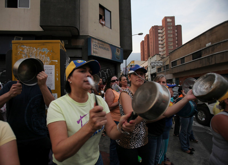 . Opposition supporters bang pots against interim President Nicolas Maduro during a protest in Caracas, Venezuela, Monday, April 15, 2013. National Guard troops fired tear gas and plastic bullets to disperse students protesting the official results in Venezuela\'s disputed presidential election which gave Maduro a very narrow victory. (AP Photo/Fernando Llano)