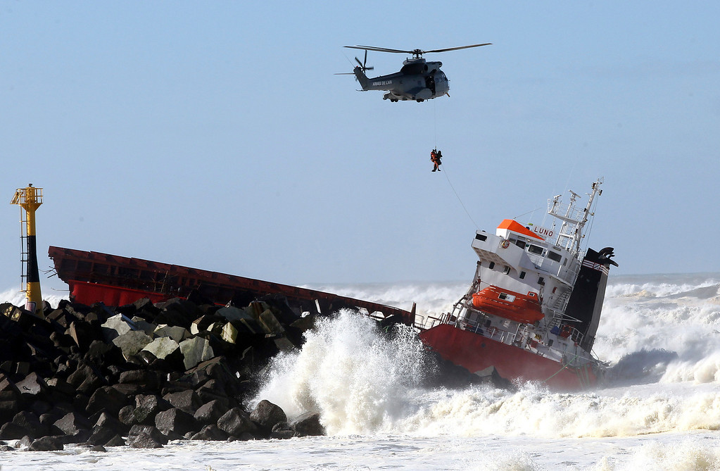 . A sailor is  lifted off by a military helicopter  after a Spanish cargo ship that slammed into a jetty in choppy Atlantic Ocean waters off Anglet, southwestern France, Wednesday, Feb. 5, 2014.  (AP Photo/Bob Edme)