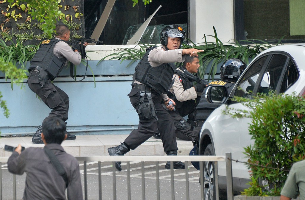 . Indonesian police take position and aim their weapons as they pursue suspects outside a cafe after a series of blasts hit the Indonesia capital Jakarta on January 14, 2016. A series of bombs killed at least three people in the Indonesian capital Jakarta on January 14, with shots fired outside a cafe as police moved in, an AFP journalist at the scene said.     AFP PHOTO / Bay ISMOYOBAY ISMOYO/AFP/Getty Images