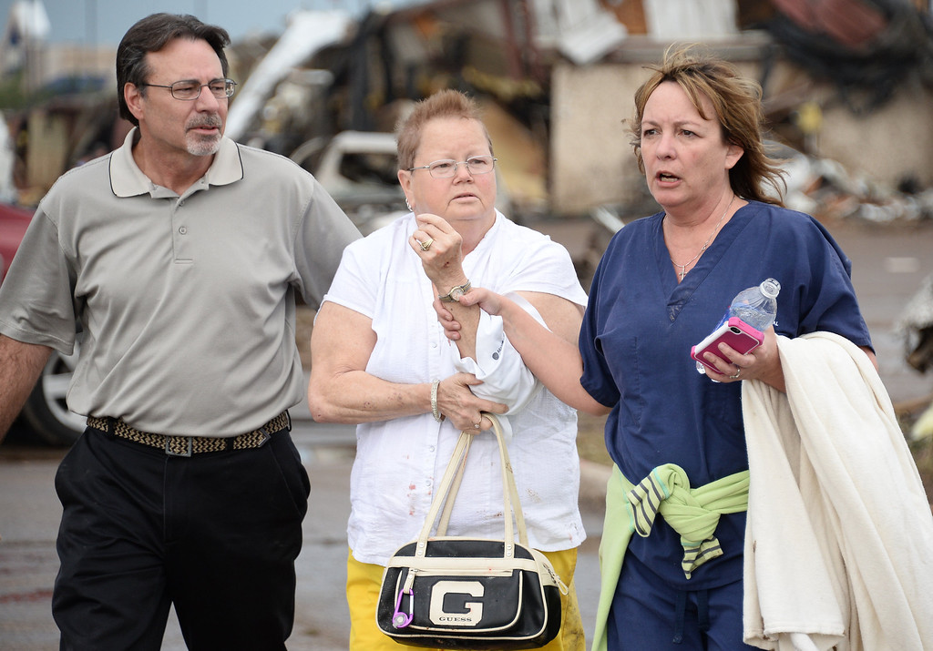 . A women is helped with a arm injury suffered during a tornado that devastated the Oklahoma City suburb of Moore on Monday, ripping up at least two elementary schools and a hospital and leaving a wake of tangled wreckage. 