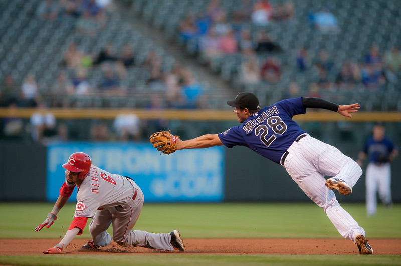 . Billy Hamilton #6 of the Cincinnati Reds slides under a tag attempt by Nolan Arenado #28 of the Colorado Rockies to reach third base on a first inning fielder\'s choice during the second game of a split double header at Coors Field on August 17, 2014 in Denver, Colorado.  (Photo by Dustin Bradford/Getty Images)