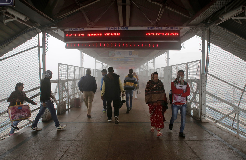 . People walk on a platform surrounded by  dense fog at a train station in Allahabad, India, Friday, Jan 6, 2017. Many trains are running behind schedule due to poor visibility caused by fog in north India. (AP Photo/Rajesh Kumar Singh)