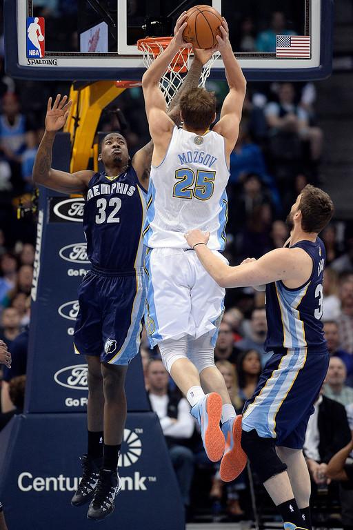 . Denver Nuggets center Timofey Mozgov (25) dunks and draws a foul as Memphis Grizzlies forward Ed Davis (32) defends during the second quarter. (Photo by AAron Ontiveroz/The Denver Post)