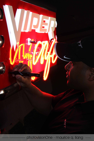 Ralph autographs this Viper Cafe sign that will be auctioned off at Ohio Region's holiday party next year.