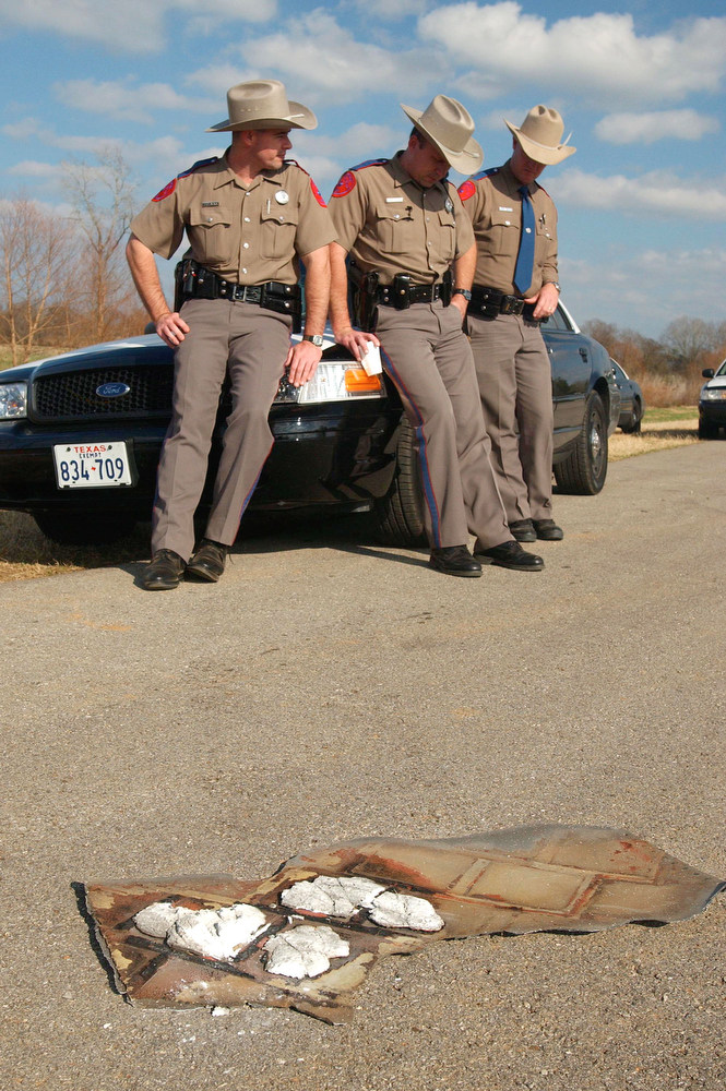 . Texas state troopers stand guard over a suspected piece of debris from the space shuttle Columbia February 2, 2003 in Douglass, Texas.  Officials combed the Texas countryside looking for pieces of the shuttle after Columbia broke apart 200,000 feet above Texas during its landing approach one day earlier.  (Photo by Chris Hondros/Getty Images)