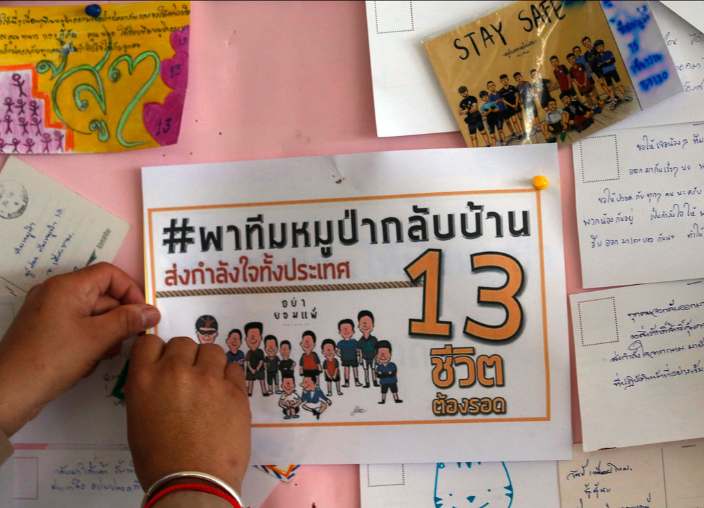 ". A Thai well wisher put poster to pray for boys and their soccer coach who have been trapped since June 23, in Mae Sai, Chiang Rai province, northern Thailand Monday, July 9, 2018. Expert divers Sunday rescued four of 12 boys from a flooded cave in northern Thailand, as a dangerous and complicated operation unfolded amid heavy rain and the threat of rising water underground. The poster reads "" Take Wild Boars back home.\"" (AP Photo/Sakchai Lalit)"
