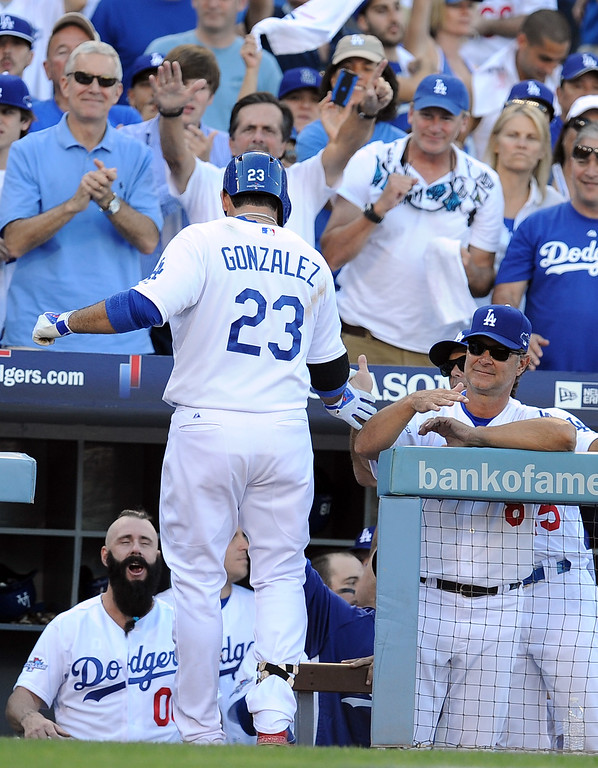 . The Dodgers\' Adrian Gonzalez enters the dugout after hitting a home run in the 8th during game 5 of the NLCS at Dodger Stadium Wednesday, October 16, 2013. The Dodgers beat the Cardinals 6-4. (Photo by Hans Gutknecht/Los Angeles Daily News)