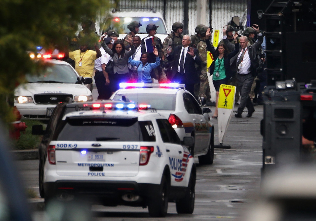 . People come out from a building with their hands up after a shooting happened at the Washington Navy Yard September 16, 2013 in Washington, DC. Police believe there to be as many as two shooters who killed several people and wounded others in an incident that put parts of the city on lockdown.  (Photo by Alex Wong/Getty Images)