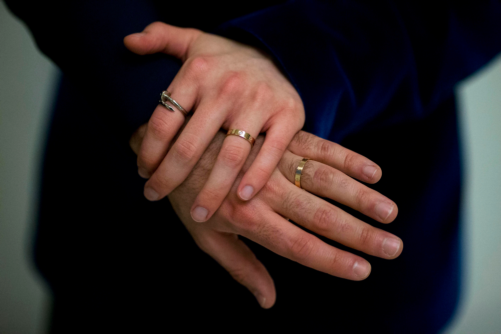 . The wedding rings of Sean Adl-Tabatabai and Sinclair Treadway are seen on their fingers as they pose for photographs after they were officially married in a wedding ceremony in the Council Chamber at Camden Town Hall in London, minutes into Saturday, March 29, 2014. Gay couples in Britain waited decades for the right to get married. When the opportunity came, some had just days to plan the biggest moment of their lives. Adl-Tabatabai, a 32-year-old TV producer from London, and Treadway, a 20-year-old student originally from Los Angeles, registered their intent to marry on March 13, the first day gay couples could sign up for wedding ceremonies under Britain\'s new law. Eager to be part of history, the two men picked the earliest possible moment - just after midnight Friday, when the act legalizing same-sex marriage takes effect. (AP Photo/Matt Dunham)