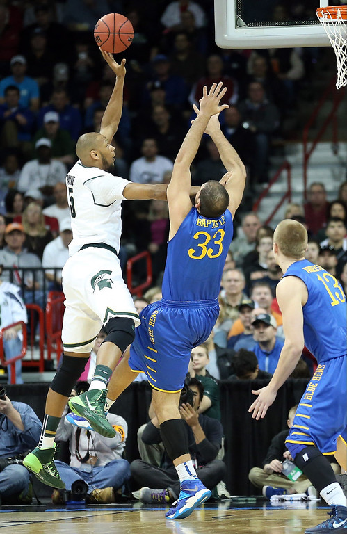 . Adreian Payne #5 of the Michigan State Spartans shoots over Carl Baptiste #33 of the Delaware Fightin Blue Hens during the second round of the 2014 NCAA Men\'s Basketball Tournament at Spokane Veterans Memorial Arena on March 20, 2014 in Spokane, Washington.  (Photo by Stephen Dunn/Getty Images)