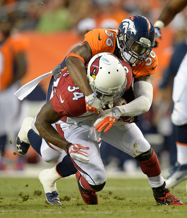 . Denver Broncos cornerback Kayvon Webster (36) tackles Arizona Cardinals running back Ryan Williams (34) during the first half on August 29, 2013 at Sports Authority Field at Mile High. The Denver Broncos hosted the Arizona Cardinals in the final game of the preseason. (Photo by John Leyba/The Denver Post)