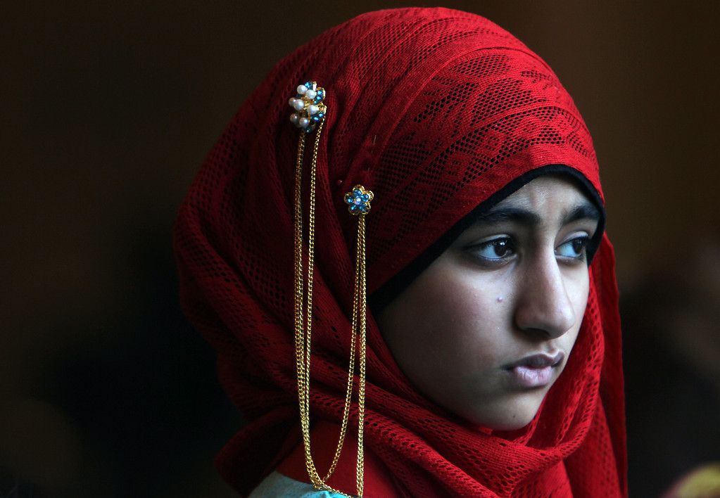 . Ayesha Dawood, 12, quietly leaves Reliant Center after the Eid ul Fitr prayer service and celebration on Thursday, Aug. 8, 2013, in Houston. (AP Photo/Houston Chronicle, Mayra Beltran)