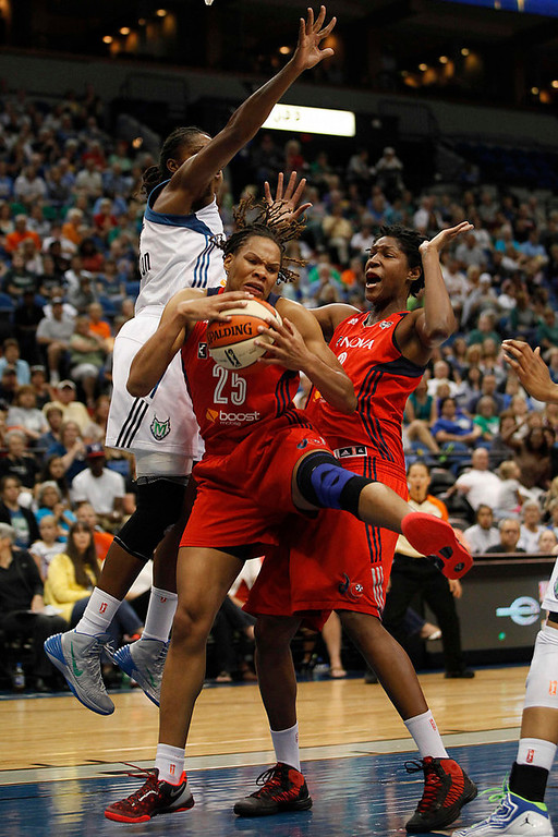 . Washington Mystics\' Monique Currie (25) grabs a rebound out of reach from Minnesota Lynx forward Rebekkah Brunson (32) in the first half.  (AP Photo/Stacy Bengs)