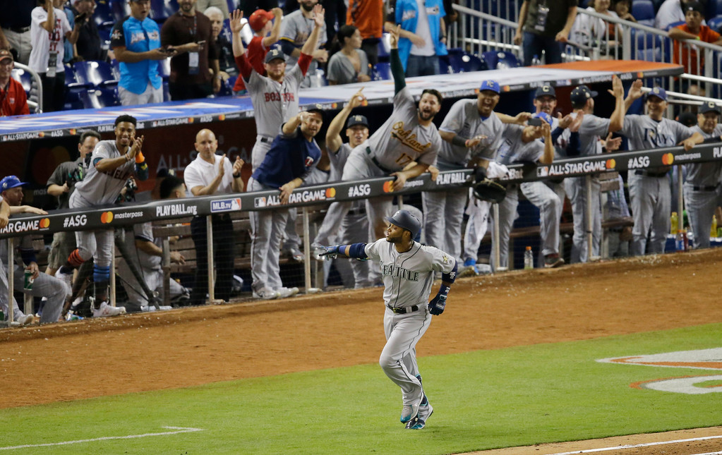 . The American League team cheer Seattle Mariners Robinson Cano (22), after he hit a home run in the tenth inning, during the MLB baseball All-Star Game, Tuesday, July 11, 2017, in Miami. The American League defeated the National League 2-1. (AP Photo/Alan Diaz)