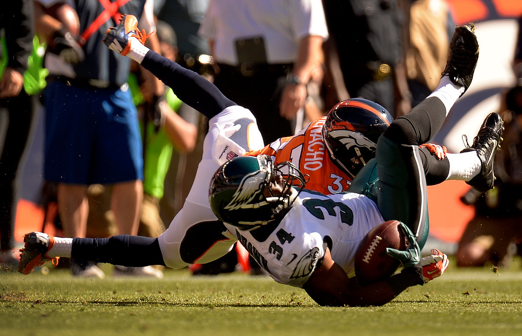 . Philadelphia Eagles running back Bryce Brown (34) is taken down byDenver Broncos strong safety Duke Ihenacho (33) during the first quarter.  (Photo by John Leyba/The Denver Post)
