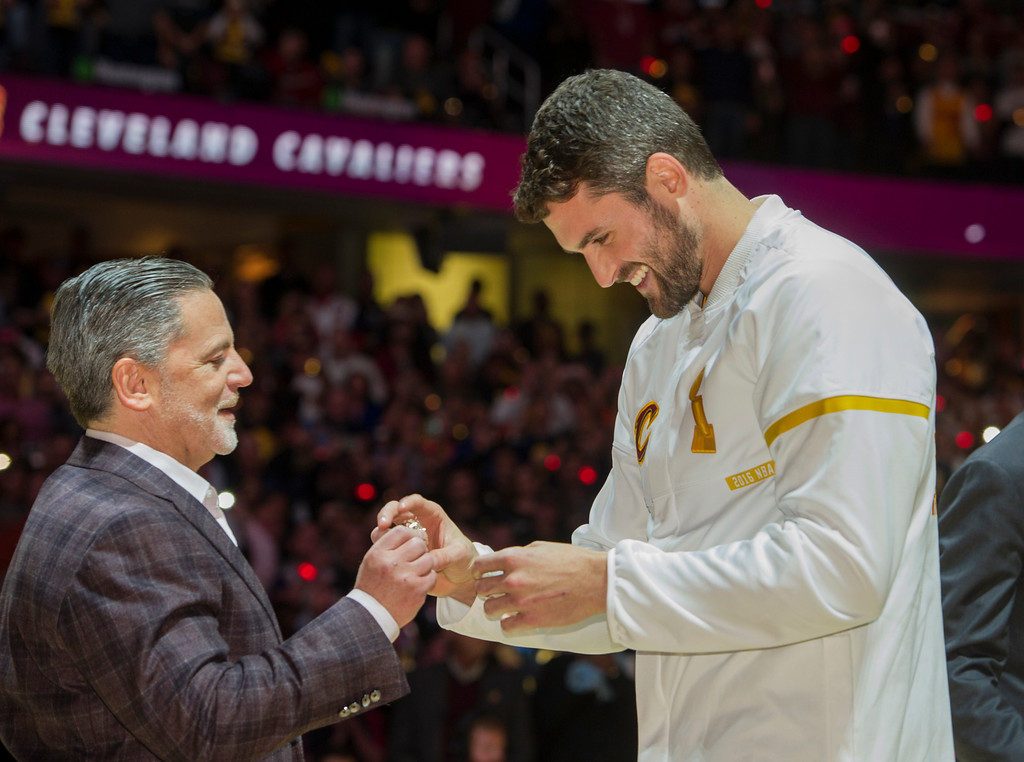. Cleveland Cavaliers\' Kevin Love accepts his NBA championship ring from Cavaliers owner Dan Gilbert before a basketball game against the New York Knicks in Cleveland, Tuesday, Oct. 25, 2016. (AP Photo/Phil Long)