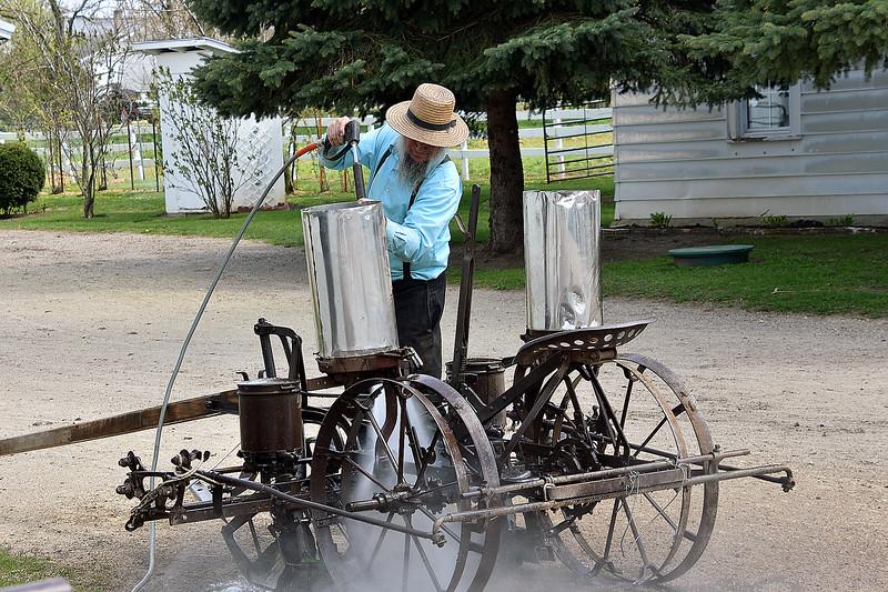 Amish man seaming cleaning his equipment-Dalton, WI -Roper.jpg