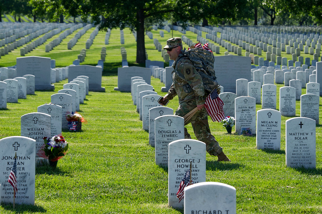. Members of the Army 3d U.S. Infantry Regiment, The Old Guard, place flags at the headstone of fallen military members during its annual Flags In ceremony at Arlington National Cemetery,  Thursday, May 24, 2018, in Arlington, Va. (AP Photo/Cliff Owen)