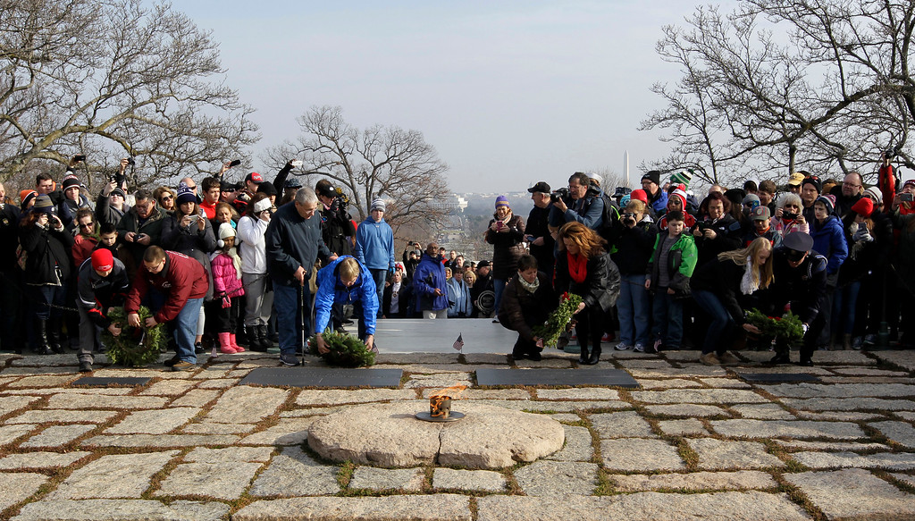 . Volunteers lay holiday wreaths at the gravesite of President John F. Kennedy during Wreaths Across America\'s 150th anniversary at Arlington National Cemetery in Arlington, Va., Saturday, Dec. 13, 2014. The Washington Monument is at right, rear, the Lincoln Memorial is at center. (AP Photo/Luis M. Alvarez)