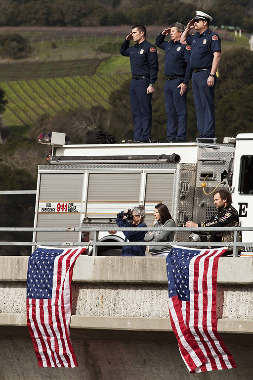 . Santa Clara firefighters (L-R) David Sosine, Bruce Ingle, and Dave Riggert salute from an overpass as the  motorcade procession honoring Santa Cruz Police Department officers Loran Baker and Elizabeth Butler travels to the officers\' memorial services in San Jose, California March 7, 2013. The two officers were killed in the line of duty February 26 while arriving at the home of a suspect they were to question.  REUTERS/Mark Avery  (UNITED STATES - Tags: CRIME LAW)