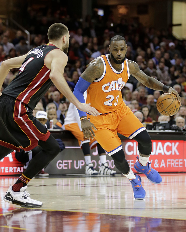 . Cleveland Cavaliers\' LeBron James (23) drives past Miami Heat\'s Josh McRoberts (4) in the first half of an NBA basketball game Friday, Dec. 9, 2016, in Cleveland. (AP Photo/Tony Dejak)