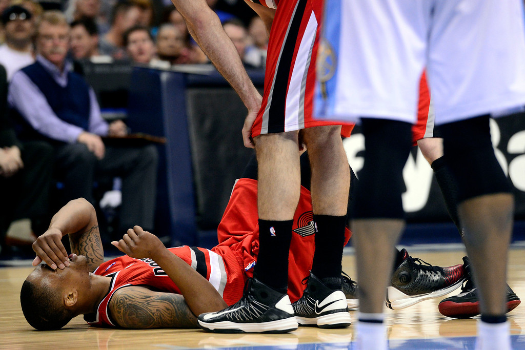 . DENVER, CO - APRIL 14: Damian Lillard (0) of the Portland Trail Blazers lays on the floor after taking contact during the second half of action. The Denver Nuggets defeat the Portland Trail Blazers 118-109 at the Pepsi Center. (Photo by AAron Ontiveroz/The Denver Post)