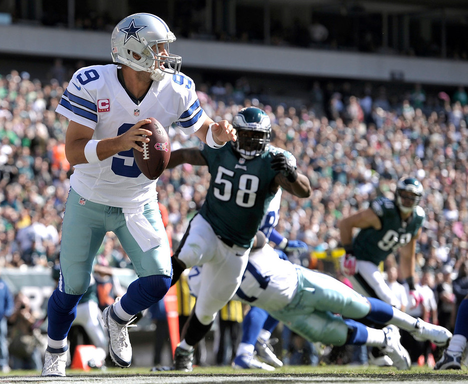 . Dallas Cowboys quarterback Tony Romo (9) looks to pass as Philadelphia Eagles outside linebacker Trent Cole (58) chases him during the first half of an NFL football game, Sunday, Oct. 20, 2013, in Philadelphia. (AP Photo/Michael Perez)
