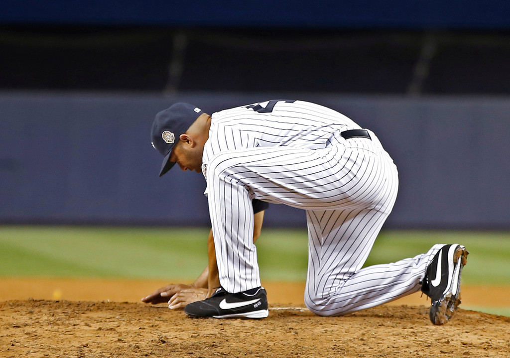 . New York Yankees relief pitcher Mariano Rivera gathers dirt from the mound after his final appearance in a baseball game at Yankee Stadium, Thursday, Sept. 26, 2013, in New York. The Yankees defeated the Tampa Bay Rays 4-0. (AP Photo/Kathy Willens)