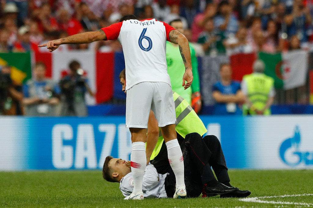 . Croatia\'s Dejan Lovren gestures to a person who invaded the pitch, bottom, during the final match between France and Croatia at the 2018 soccer World Cup in the Luzhniki Stadium in Moscow, Russia, Sunday, July 15, 2018. (AP Photo/Matthias Schrader)