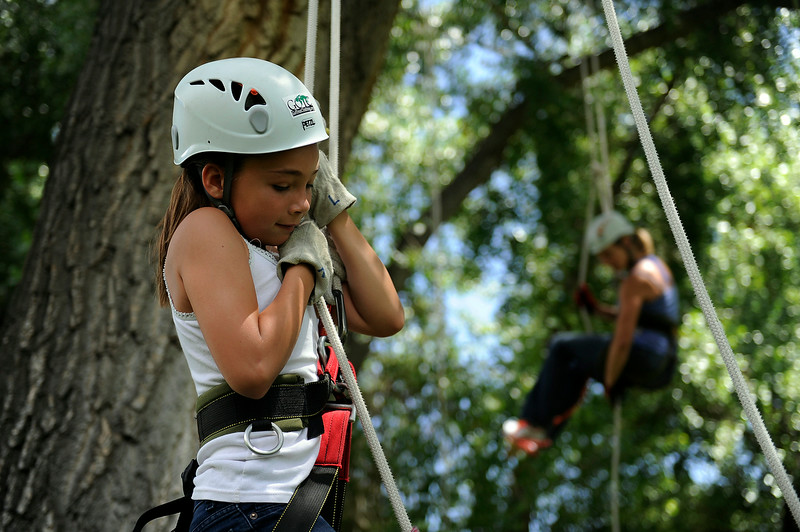 ". Bailey Williams,10, adjusts the top knot of her rope as she climbs a cottonwood tree during a tree climbing class at Grampas Park in Golden, Colorado on June 26, 2014. Harve Teitelbaum will be leading a tree climbing course called ""Dances with Branches\"" through Golden Parks and Recreation starting July 5. (Photo by Seth McConnell/The Denver Post)"
