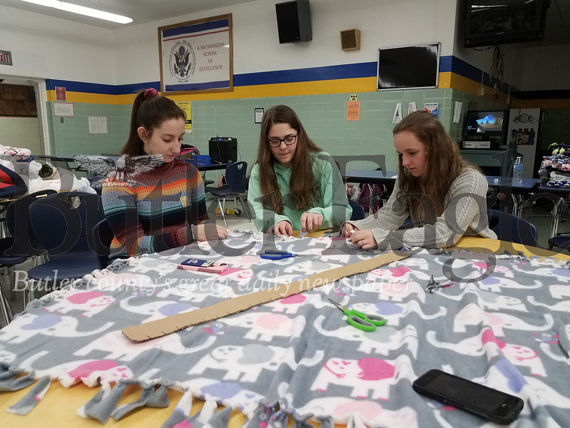 Freeport High school seniors, from left, Madison Wagner, Maria Giancola and Autumn Kriebel work on comfort blankets in the high school cafeteria.