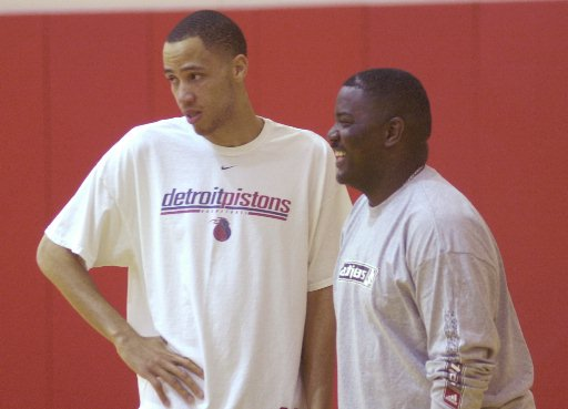 Description of . Detroit Pistons forward Tayshaun Prince, left, and team president Joe Dumars watch during the media availability at the team's practice facility in Auburn Hills, Mich., Wednesday, June 9, 2004. (AP Photo/Carlos Osorio)