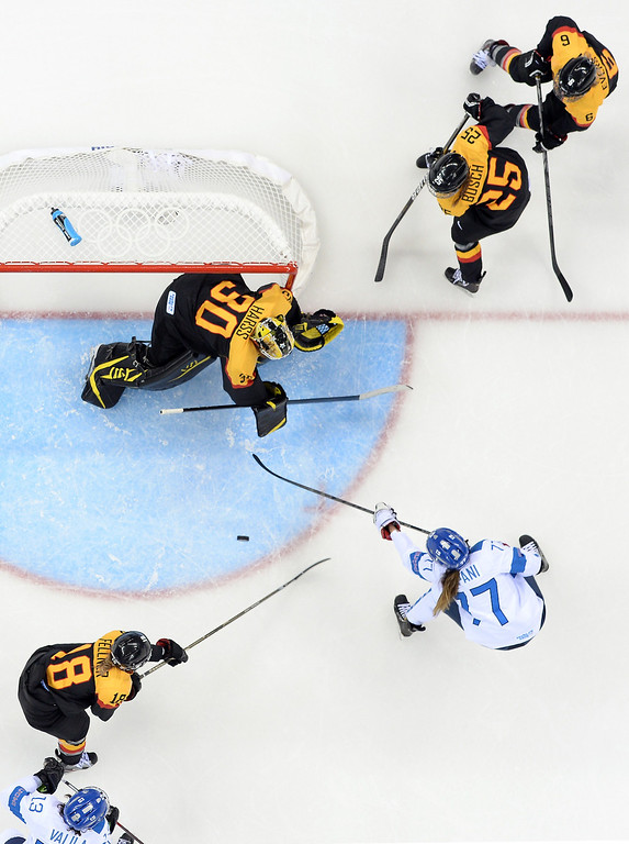 . Finland\'s Susanna Tapani (C-R) vies with Germany\'s goalkeeper Jennifer Harss during the Women\'s Ice Hockey 5th- 8th place classifications match between Finland and Germany at the Shayba Arena during the Sochi Winter Olympics on February 16, 2014.  JONATHAN NACKSTRAND/AFP/Getty Images