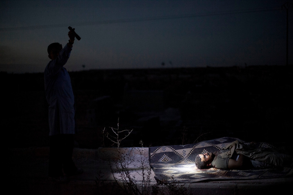 . FILE - A man points a flashlight toward the body of a Syrian man killed from Syrian Army shelling at a graveyard in Aleppo, Syria, Saturday, Oct. 13, 2012. (AP Photo/Manu Brabo, File)