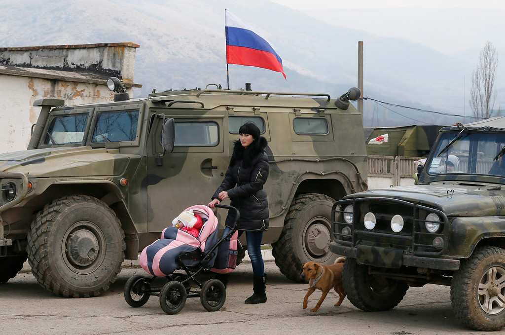 """. A woman walks with her baby in front of Russian \'GAZ Tigr\' infantry mobility vehicle outside the territory of Ukrainian military unit in the village of Perevalnoye, outside Simferopol, Ukraine, 12 March 2014. Crimea\'s secessionist authorities said on 12 March that they have partially closed the region\'s airspace to \""""keep out provocateurs\"""" in the run-up to the March 16 referendum about joining Russia.  EPA/YURI KOCHETKOV"""