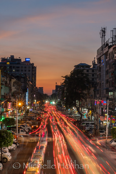 YANGON, MYANMAR - DECEMBER 15, 2018: Traffic flows through the city streets at dusk.