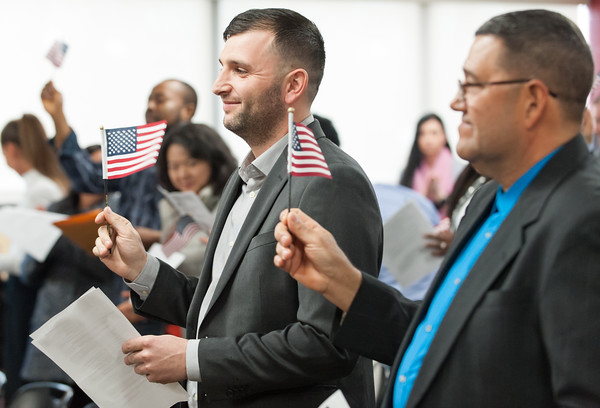 04/10/18 Wesley Bunnell | Staff Dritero Ferati, middle, from Macedonia waves an american flag along with other new citizens including Tito Fernandez Benitez from Paraguay, R, during a naturalization ceremony on Tuesday afternoon at the New Britain Public Library.