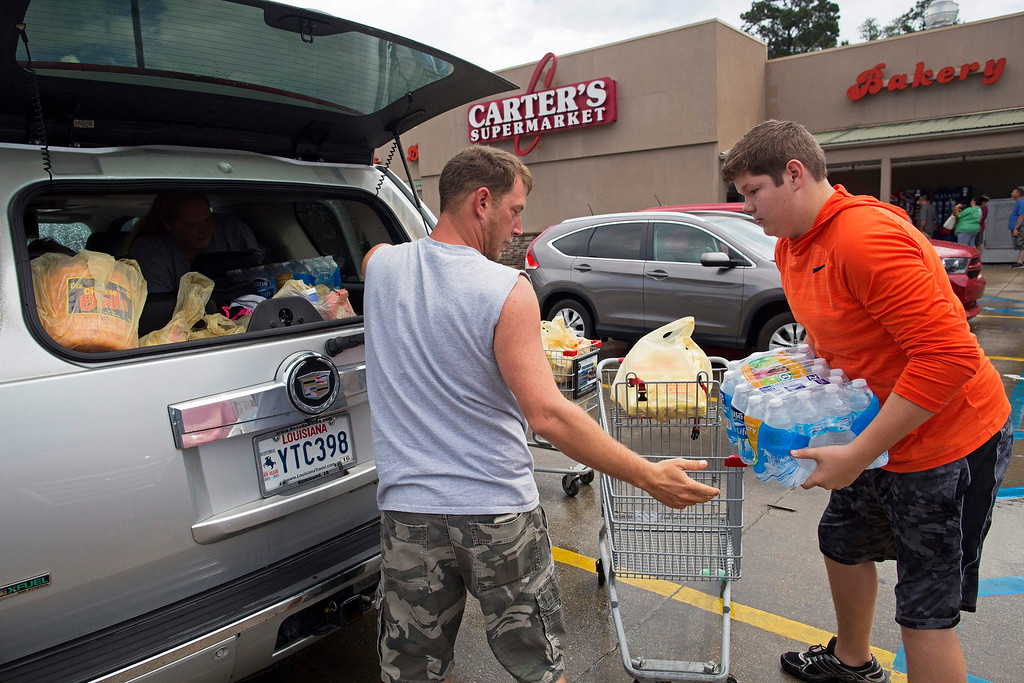 . Eli Turnage, 14, right, helps Thomas Creel load his groceries at the Carter\'s Supermarket in Livingston, La., Monday, Aug. 15, 2016. The store opened for the first time today since flooding started in the region. Turnage is volunteering at the supermarket to keep himself busy after his home was destroyed from the flooding. The Creel family was stocking up before returning to their flood damaged home. (AP Photo/Max Becherer)